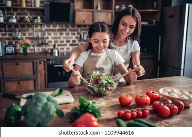 portrait of happy mother helping her daughter tossing the salad in the bowl on the kitchen