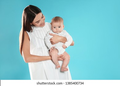 Portrait of happy mother with her baby on color background. Space for text