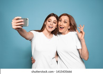 Portrait of happy mother with her daughter taking selfie on color background