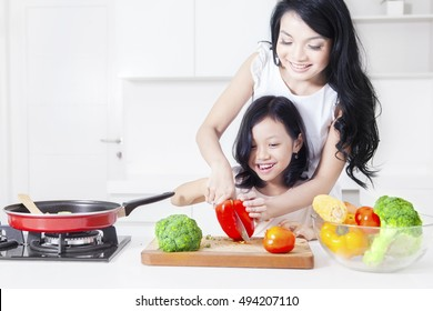Portrait of happy mother and her daughter cooking together in the kitchen while cutting vegetable
