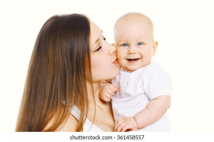 Portrait happy mother kissing her cute baby over white background