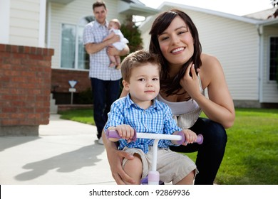 Portrait of happy mother sitting besides her son with in background