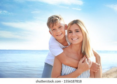 Portrait of happy mother and son on sea beach