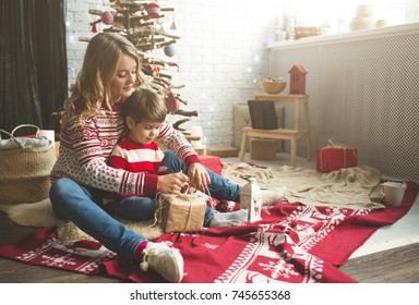 Portrait of happy mother and son on the background of the Christmas tree in new year room. The idea for postcards