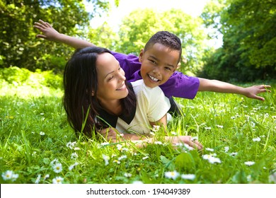 Portrait of a happy mother and son playing outdoors in the park