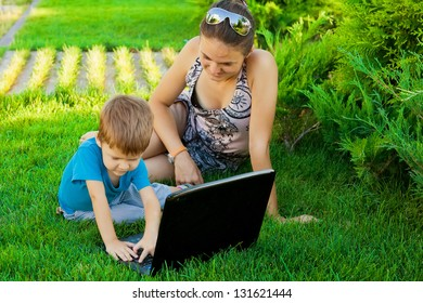 Portrait of happy mother and son using laptop outdoor sitting on the grass together