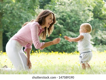 Portrait of a happy mother teaching baby to walk in the park