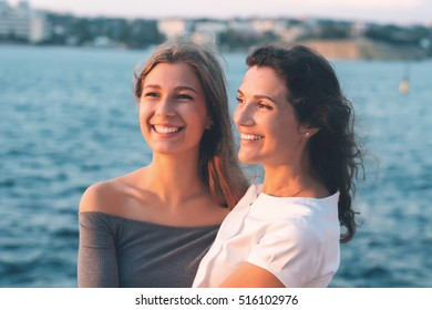 Portrait of happy mother with teenage daughter. Sunset light. Mom holding her teen daughter.