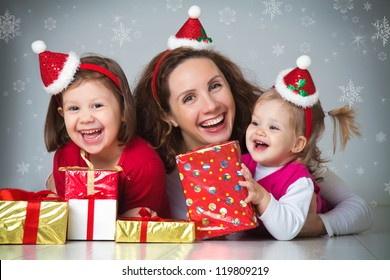 Portrait of happy mother with two cute daughter in Christmas hat