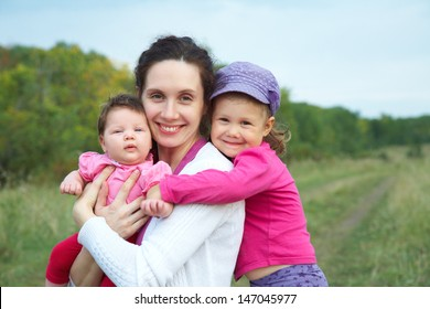 portrait of happy mother with two cute little daughters outdoors