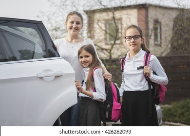 Portrait of happy mother and two girls with school bags posing at the car