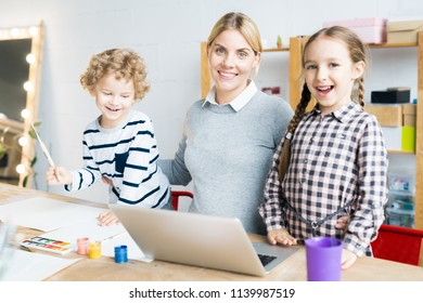 Portrait of happy mother working on laptop while her two kids drawing