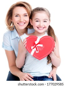 Portrait of happy mother and young daughter hold gift for birthday  - isolated