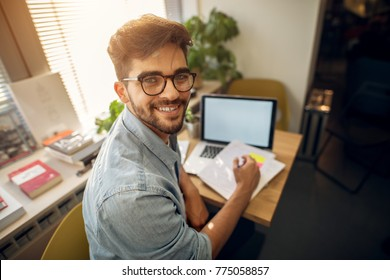 Portrait of happy motivated smiling hipster student learning for a test or an exam at high school library desk while sitting turn backwards and looking at the camera.