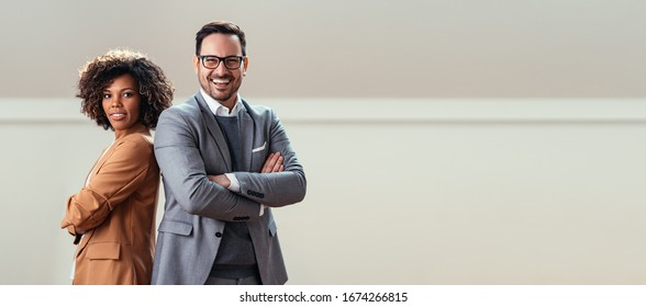 Portrait of happy multi ethnic business couple posing with arms crossed