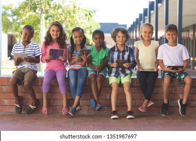 Portrait of happy multi ethnic students sitting with digital tablet on brick wall at corridor in school