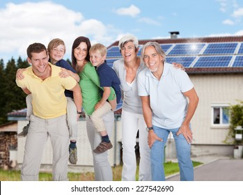 Portrait of happy multi generation family standing against home
