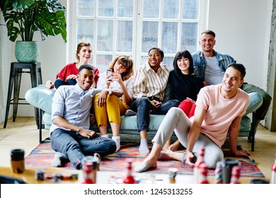 Portrait of happy multicultural young people dressed in casual wear resting together at home apartment sitting on cozy sofa.Cheerful hipster guys laughing and relaxing in flat on weekend