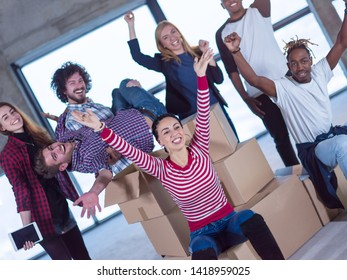 portrait of happy multiethnic business team with cardboard boxes around them during movin in at new unfinished startup office building