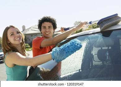 Portrait of a happy multiethnic couple washing car together
