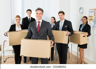 Portrait Of Happy Multiethnic Employees In Office Holding Cardboard Boxes