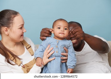 Portrait of happy multiethnic family sitting on couch at home and looking at camera. Black father, white mother and their adorable baby daughter. Father gently pulling her ears for fun.