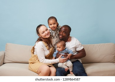Portrait of happy multiethnic family sitting on couch at home and looking at camera. Black father, white mother and two daughters. Hugging each other.