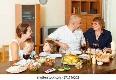 Portrait of happy multigeneration family communicate over holiday table at home interior