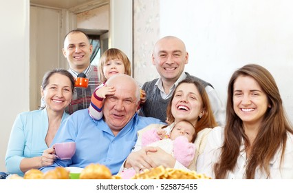 Portrait of happy multigeneration family communicate over tea at home