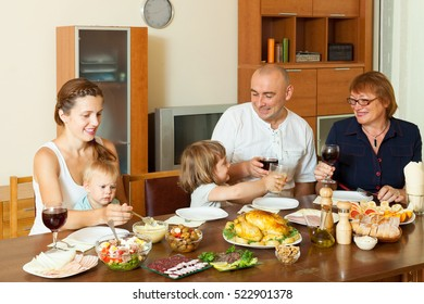 Portrait of happy multigeneration family  eating chicken at home together