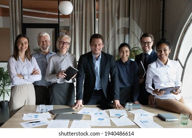 Portrait of happy multiracial businesspeople stand pose at workplace in modern office. Smiling diverse multiethnic employees colleagues show leadership unity. Success, employment concept. - Shutterstock ID 1940486614