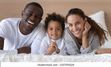 Portrait of happy multiracial young family look at camera lying on cozy white bed at home, smiling international mom and dad relax with little biracial boy child posing for picture in bedroom