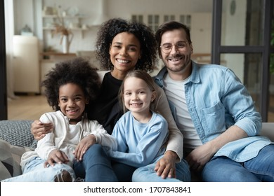 Portrait of happy multiracial young family with little daughters sit on couch look at camera posing, smiling multiethnic parents cuddle hug with small kids girls, enjoy weekend quarantine at home