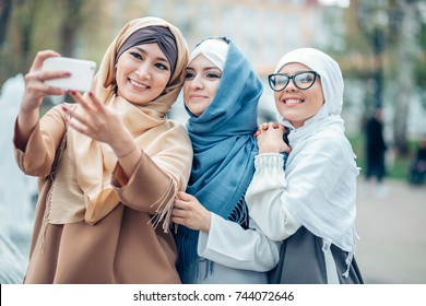 Portrait of happy muslim female making selfie together outdoor