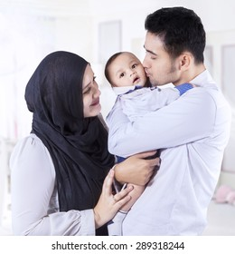 Portrait of happy muslim parents with their 0-3 months baby standing in the bedroom at home