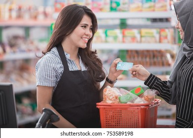 portrait of happy muslim woman paying her shopping with credit card in grocery store
