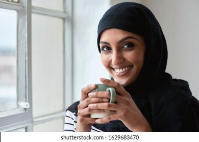 Portrait happy muslim woman smiling by window holding coffee wearing hijab headscarf