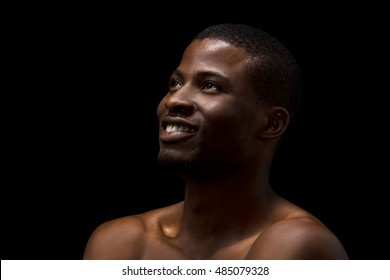 Portrait of happy naked black man smiling for camera while posing over black background in studio. Handsome man looking upwards.
