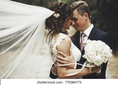 Portrait of happy newly wife and husband hugging outdoors and smiling, with waving veil and wedding bouquet made of white peonies. Sincere feelings of two young people. Concept of true immortal love.