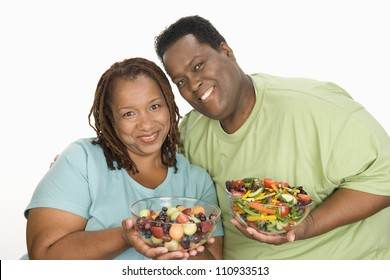 Portrait of happy obese couple holding bowl of salads isolated over white background