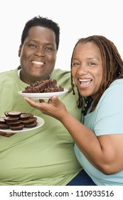 Portrait of happy obese couple holding biscuits isolated over white background