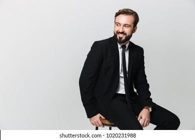Portrait of happy office worker in black suit smiling while sitting on chair and looking aside on copyspace isolated over white wall
