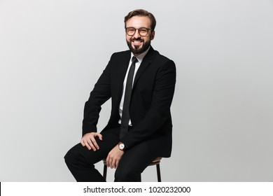 Portrait of happy office worker in black suit smiling while sitting on chair and looking on camera isolated over white wall
