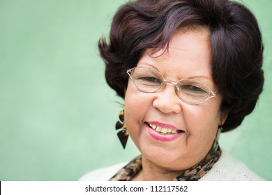 Portrait of happy old african american woman with glasses and wig smiling at camera