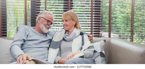 Portrait of happy old couple smiling in living room at home, caucasian senior couple relax in sofa. Healthcare lifestyle elderly retirement together true love valentines day concept panoramic banner