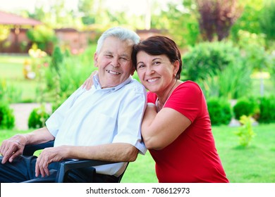 Portrait of happy old father and his 50 years daughter at home garden