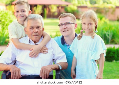 Portrait of happy old grandfather and cute children in summer