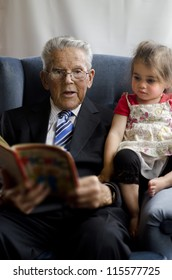 Portrait of happy old man read a book to his grandchild in his 90's.