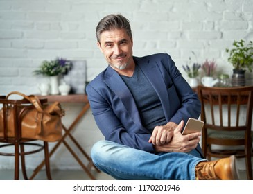 Portrait of happy older white man with gray hair wearing jacket smiling holding smart phone.   .