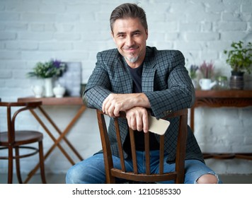 Portrait of happy older white man with gray hair wearing jacket smiling using smart phone.   .